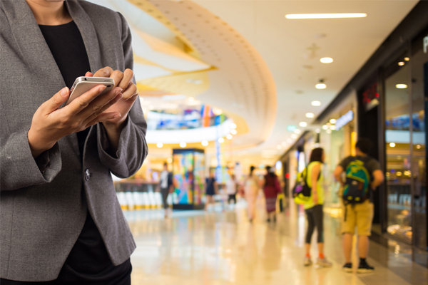 Image of Person Holding a Mobile Phone to Show 4 Ways Retailers Use Mobile For Better Customer Experiences